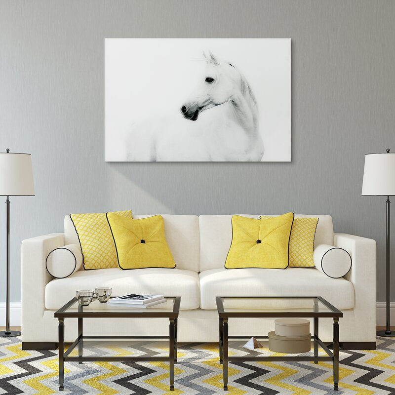 A white sofa with yellow throw pillows and a photograph of a white stallion above it.
