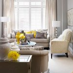 A living room with gray interiors and splashes of yellow.