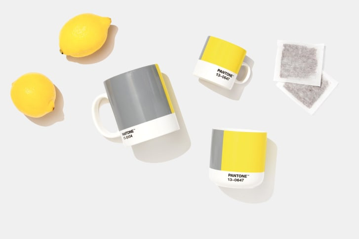 A few Pantone mugs in varied sizes with the colors of the month, tea bags, and lemons.