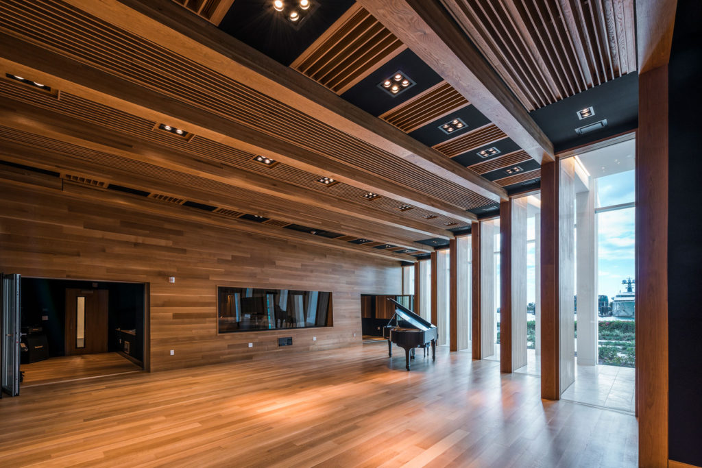 Interoir of the Sanctuary music studio covered in wood with a grand piano.