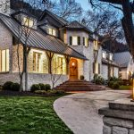 Beautiful home with sloping roof, stone exterior, and arched wooden door.