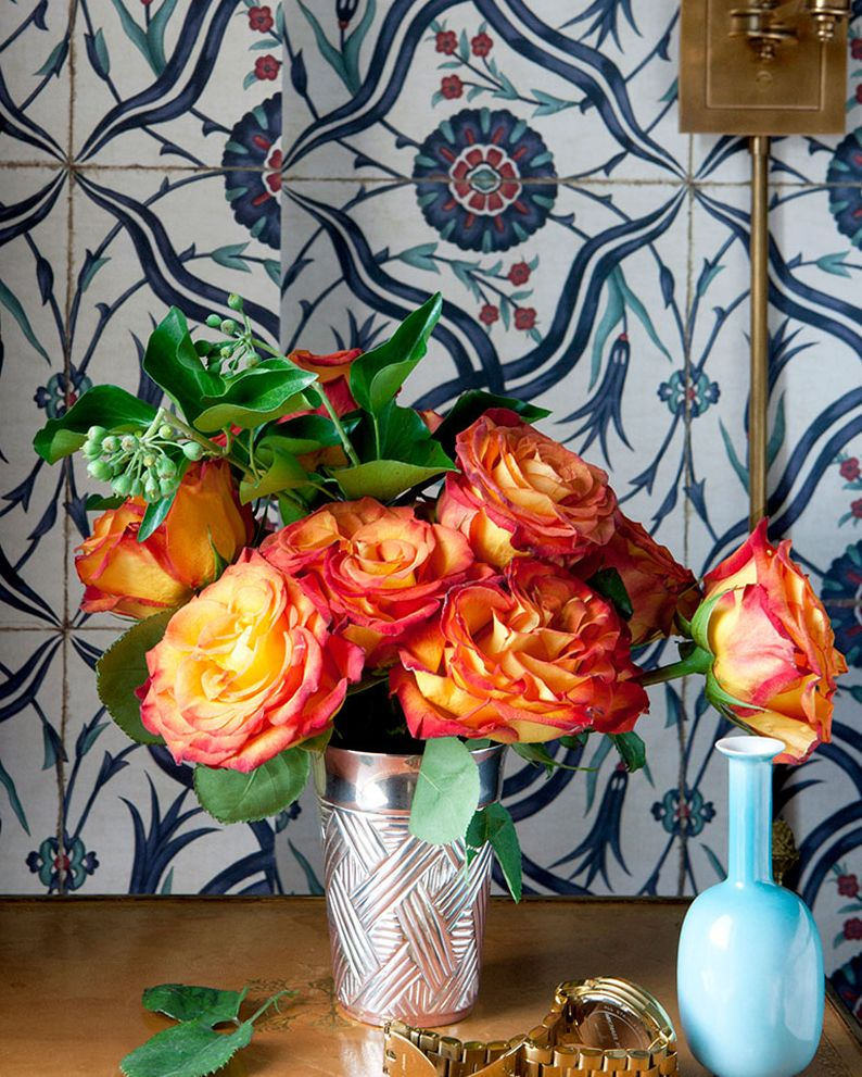 Bright colored orange flowers in a silver metallic vase.
