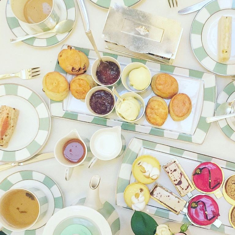 An top view shot of a table filled with breads, jams, desserts, and tea.