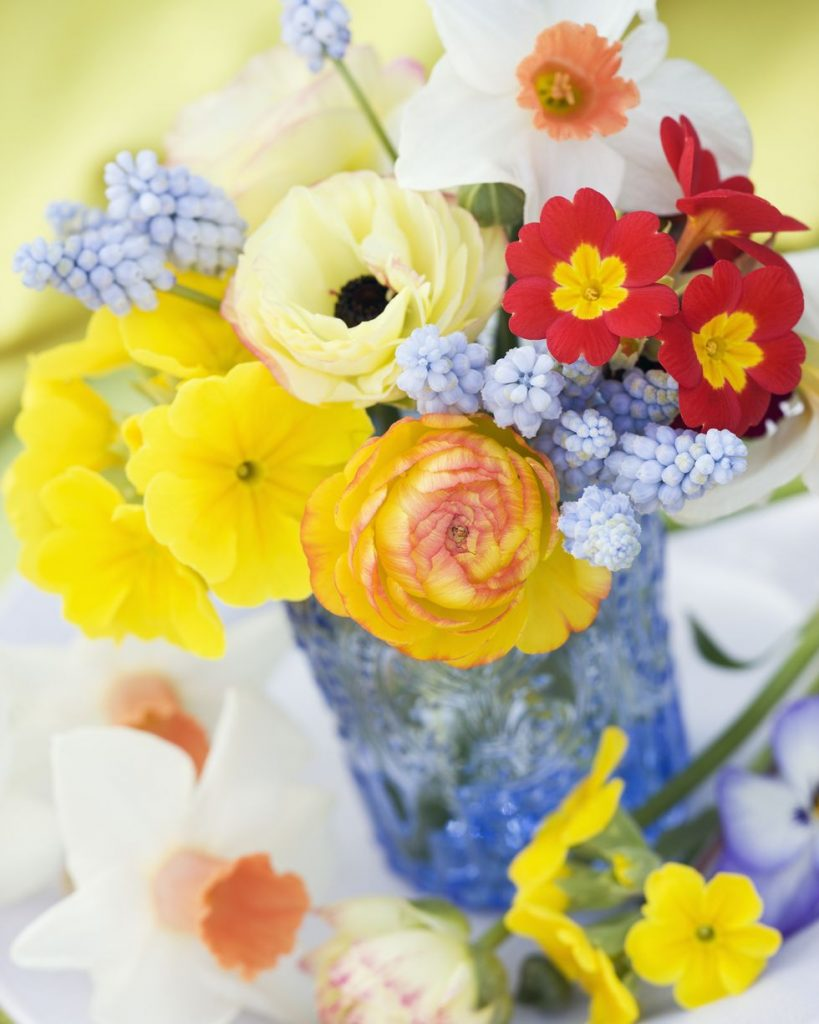 Close-up of an eclectic mix of flowers in a blue vase.