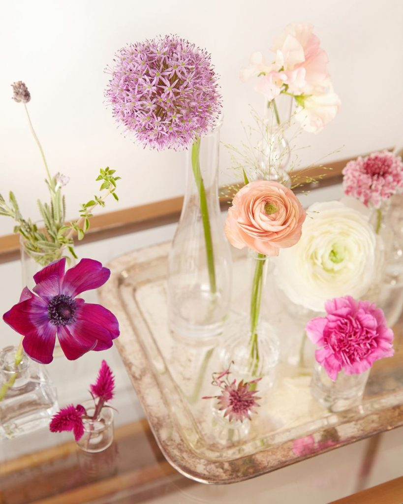 A variety of spring flowers in individual bud vases.