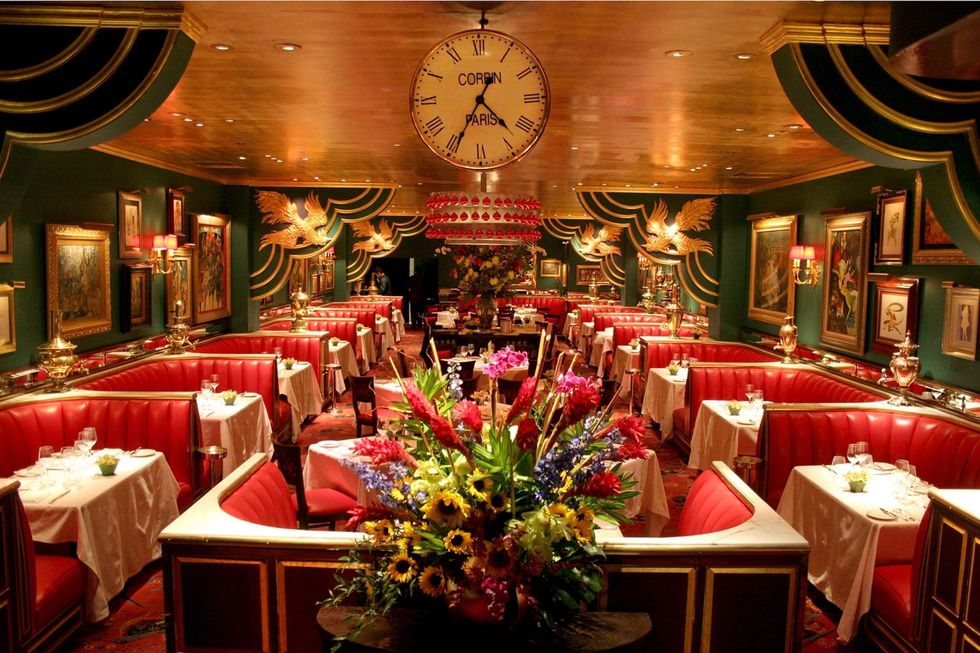 An opulent tea room with red banquette seating and gold details.