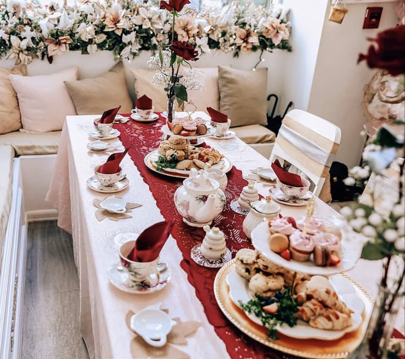 A long table set up with teacups, towers of finger foods, and floral decor all around.