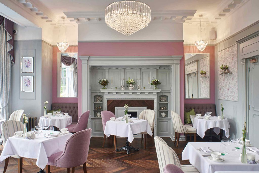 A tea room area with pink accent walls and chairs.