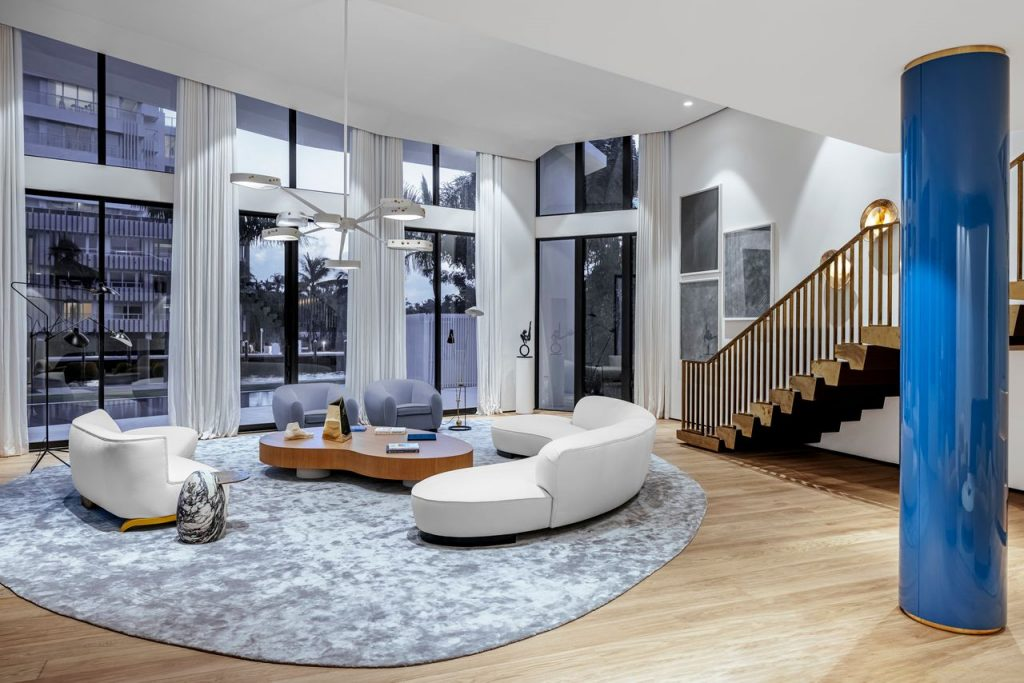 A living room area with large floor to ceiling windows, a luxe bronze staircase, and blue column.