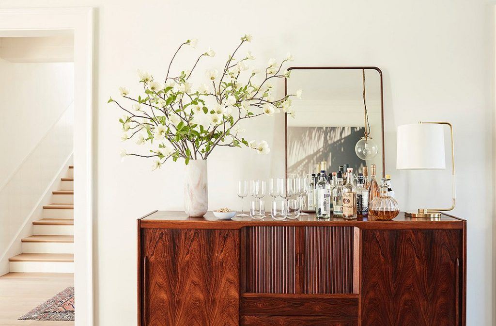 A vase filled with apple blossom branches on a mid-century modern style bar console.
