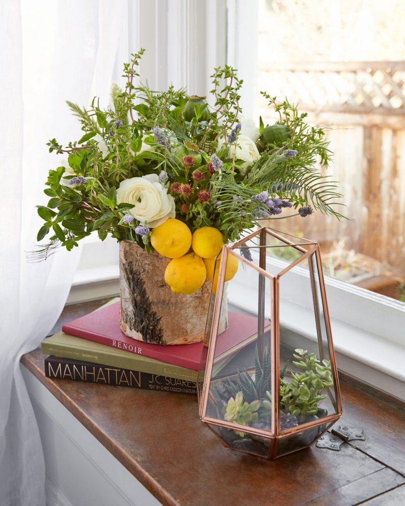 A floral arrangement with a lot of greenery, white flowers, and whole lemons in a birch vase.