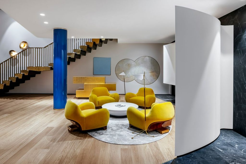 Living room area with large yellow seating with bronze staircase and blue column.