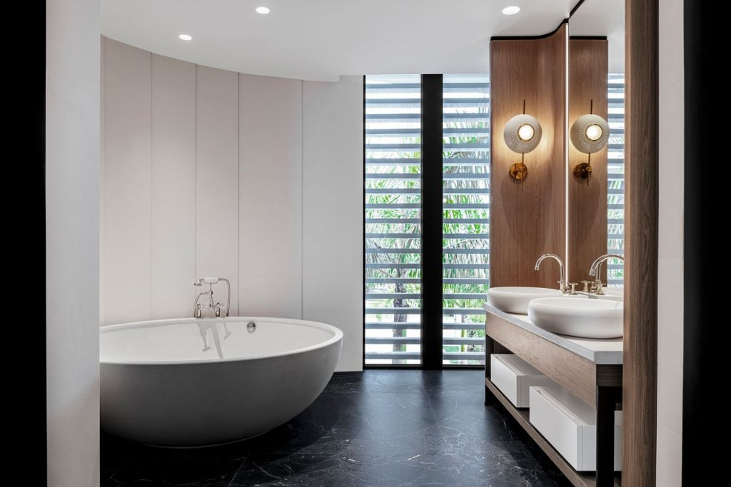 Minimal bathroom with large round freestanding tub and round sinks.