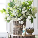 A white floral arrangement with stick and twine vase.
