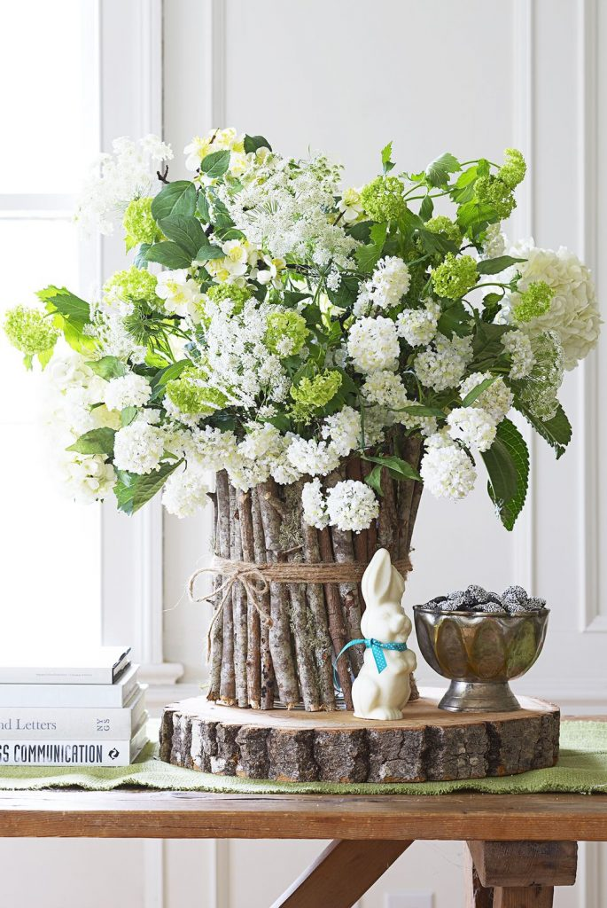 A white floral arrangement in a vase made from sticks and twine.