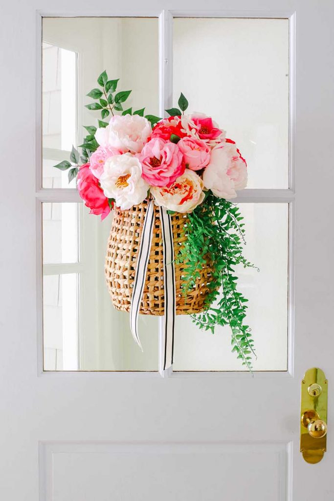 A women basket of peonies and greenery hung on a white door with gold handle.