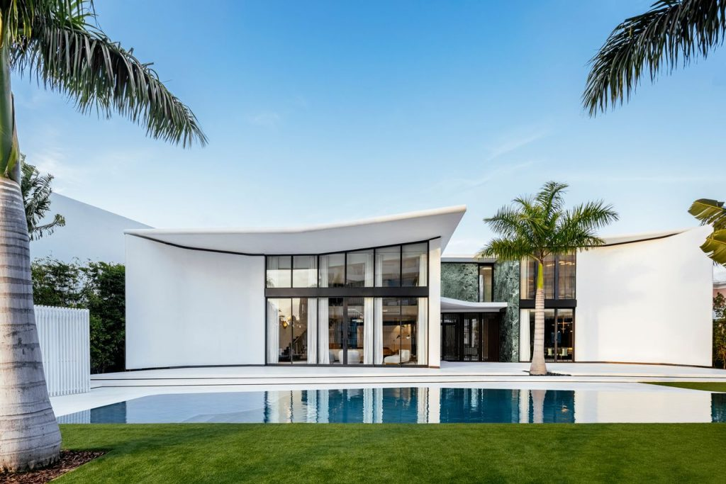 White exterior of a Miami mini-mansion with green marble accents and curvilinear lines.