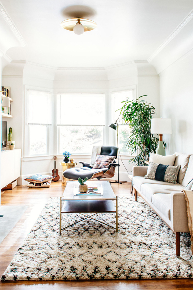 A living room with a leather chair, ottoman, and shaggy, patterned rug.