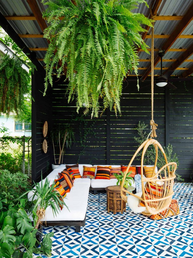 A gazebo area with black slat siding, colorful stenciled flooring, an outdoor sectional, and a swing chair.