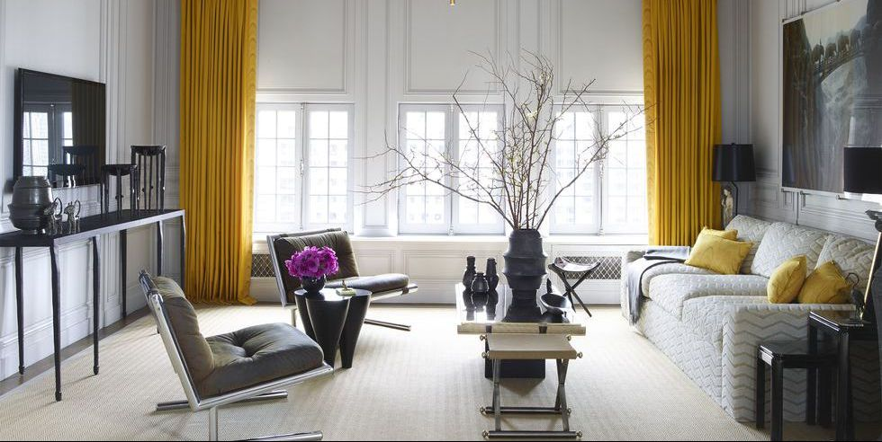 A living room with yellow curtains hung high.