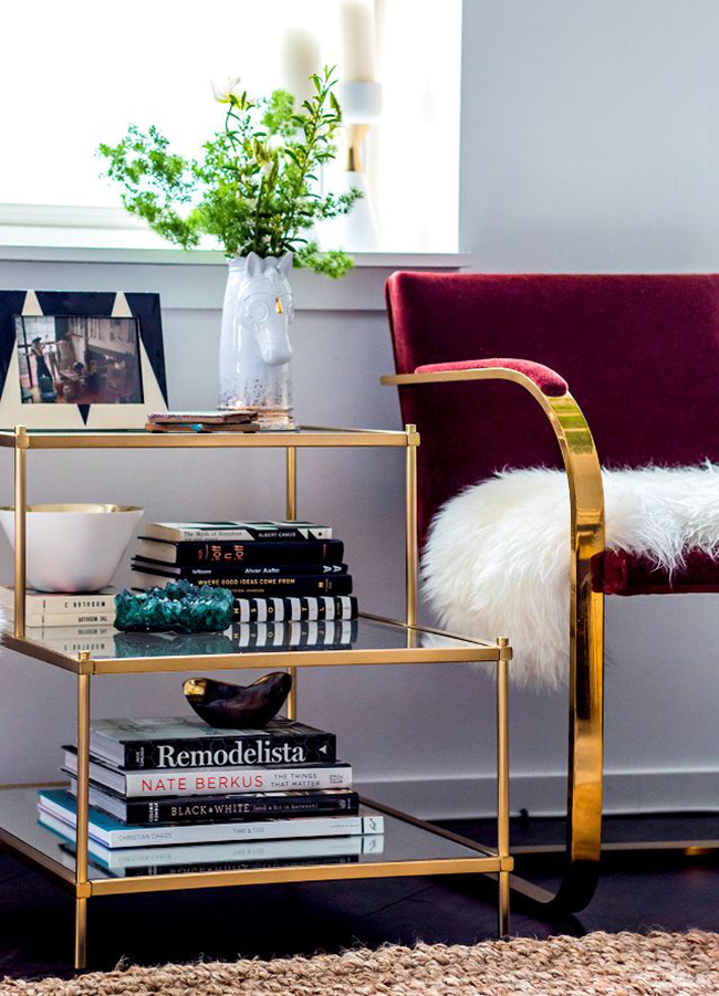 A close up of a gold end table and chair with gold accents.