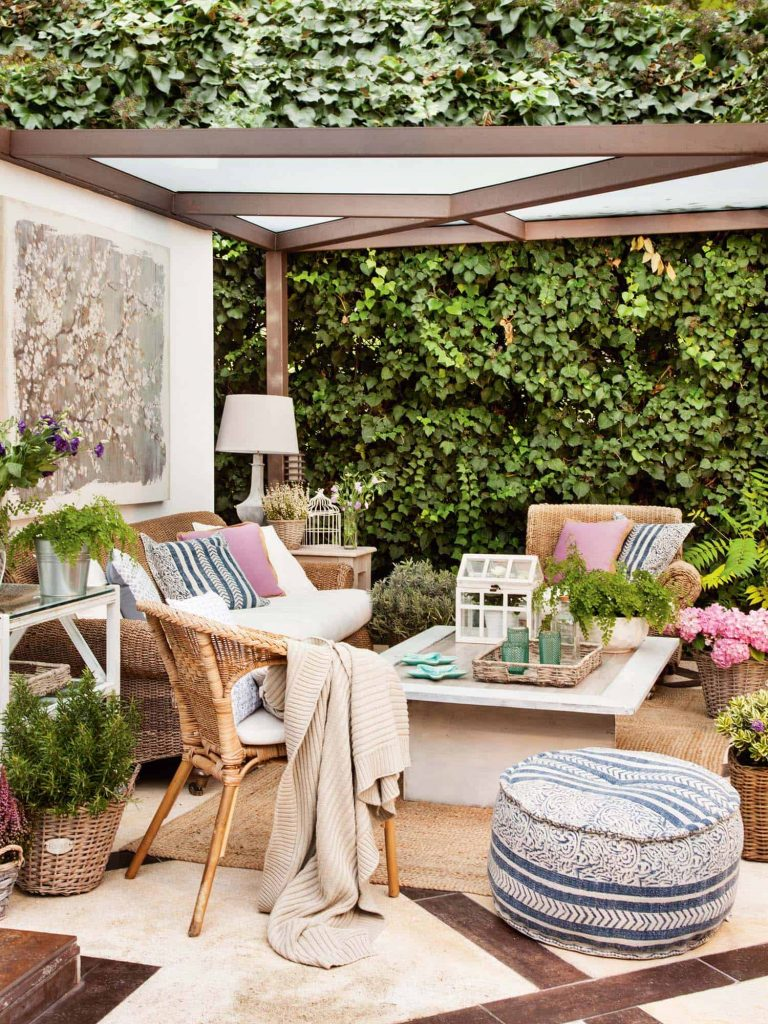 An outdoor living room with a wall of greenery and a pouf chair.