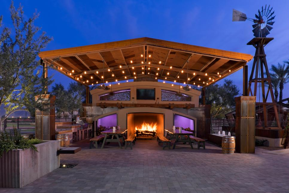 A large gazebo with picnic tables and a fireplace in the center.