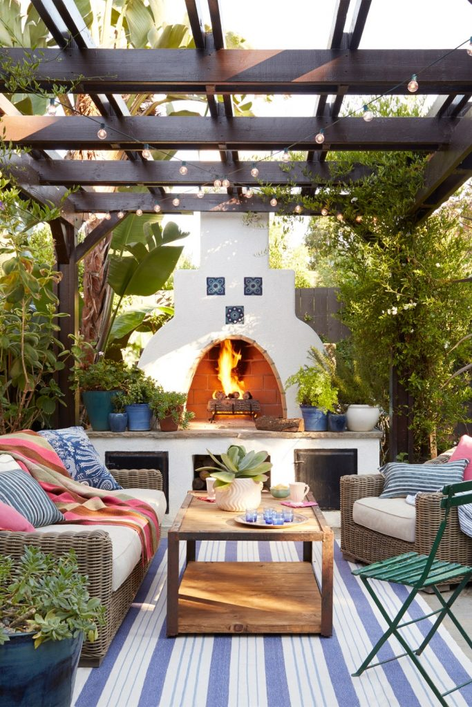 A pergola nearby a fireplace, outdoor furniture, and a blue striped rug.