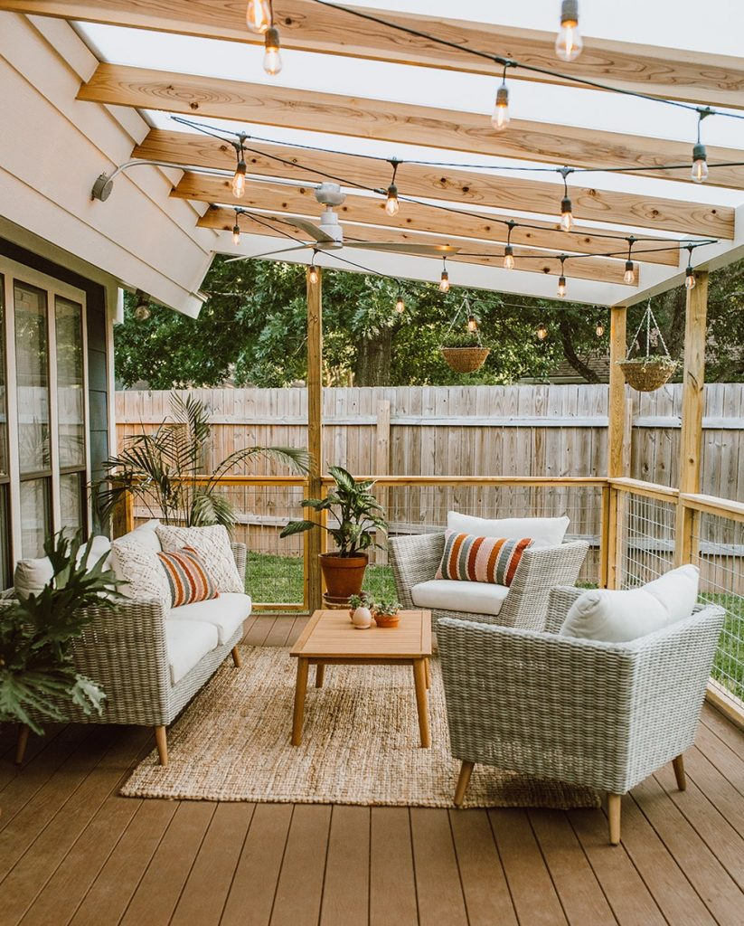 A pergola as an outdoor extension to a home with outdoor furniture and string lights hanging from above.