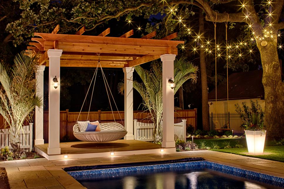A poolside pergola with a loveseat swing hanging from it.