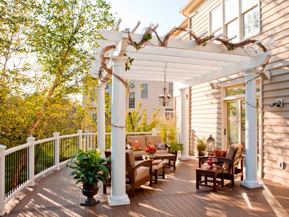 Outdoor furniture underneath a white pergola with white columns.