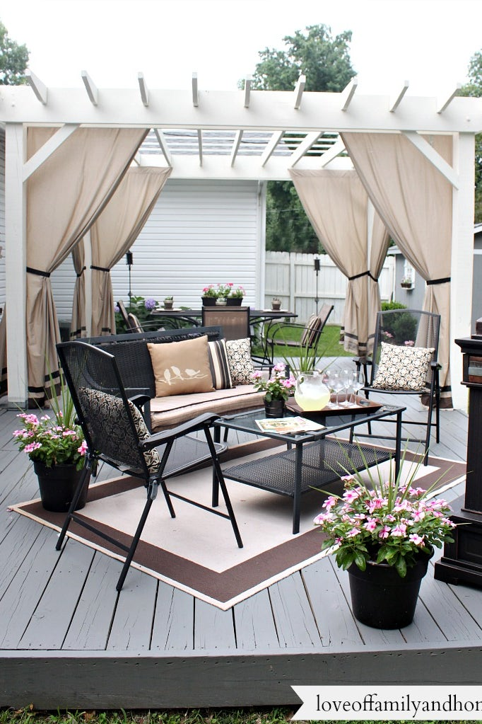 A white pergola with black outdoor furniture and neutral colored curtains and accents.