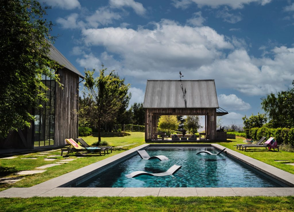 Open pool area with curved floating lounge chairs and barbecue pavilion in the back.