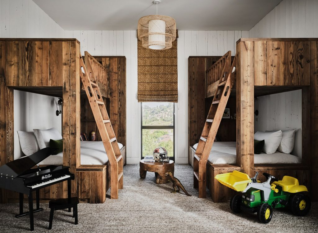 Guest bedroom with two mirrored bunk beds, mini grand piano, toy vehicle, dinosaur, and helmet.