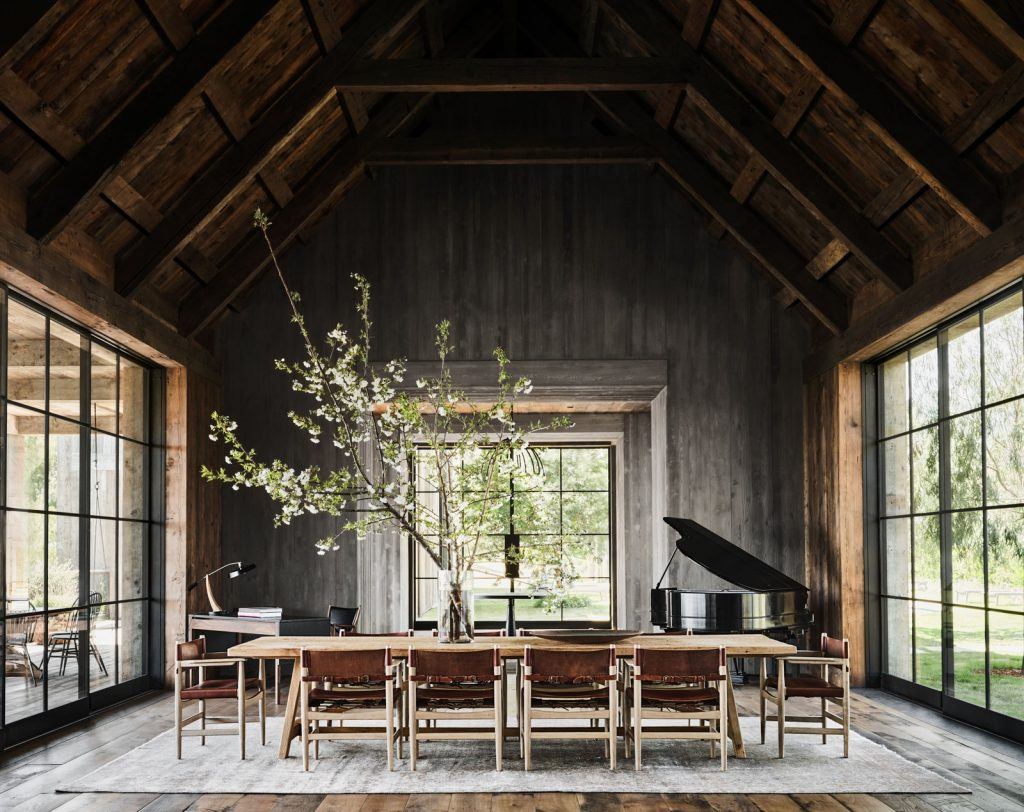 Dining room with long dining room table, leather chairs, and large floral branches.