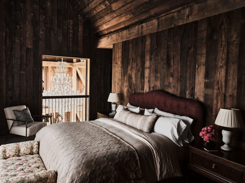 An intimate guest bedroom with dark wooden plank and bed with wine-colored headboard.