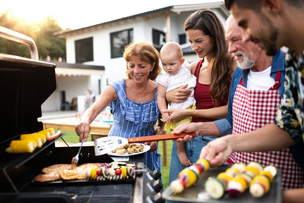 Multi-generational family members gathered by a grill.