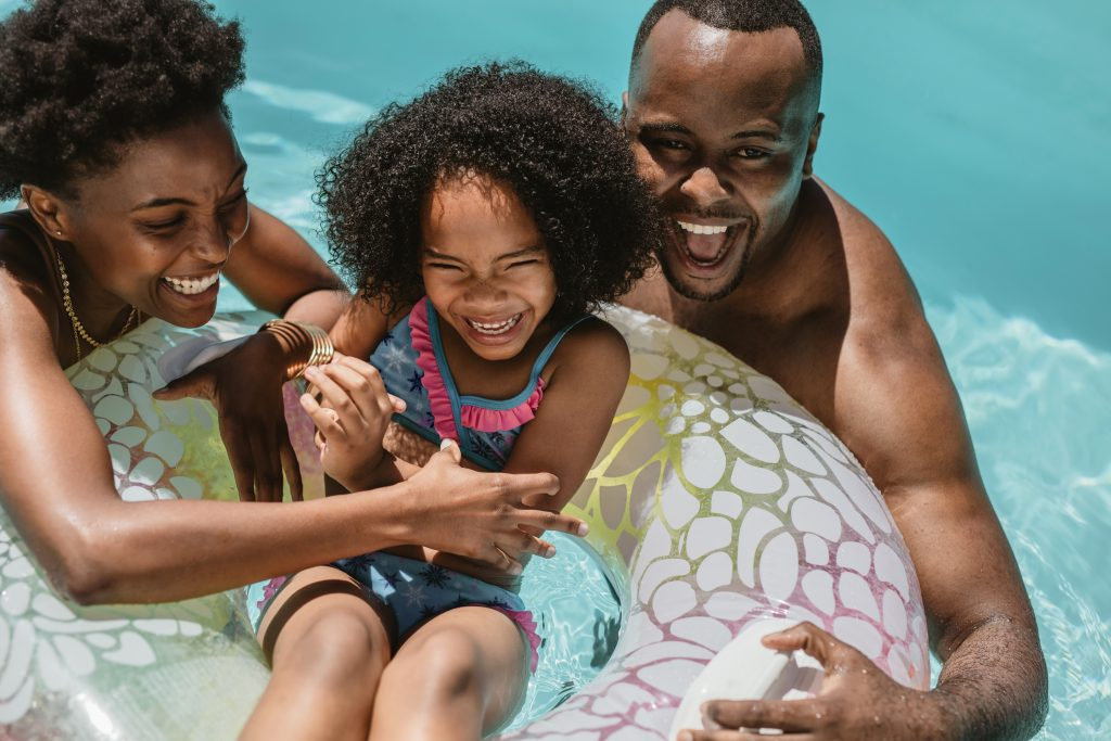 An African American couple enjoying the pool with their daughter in a pool float.