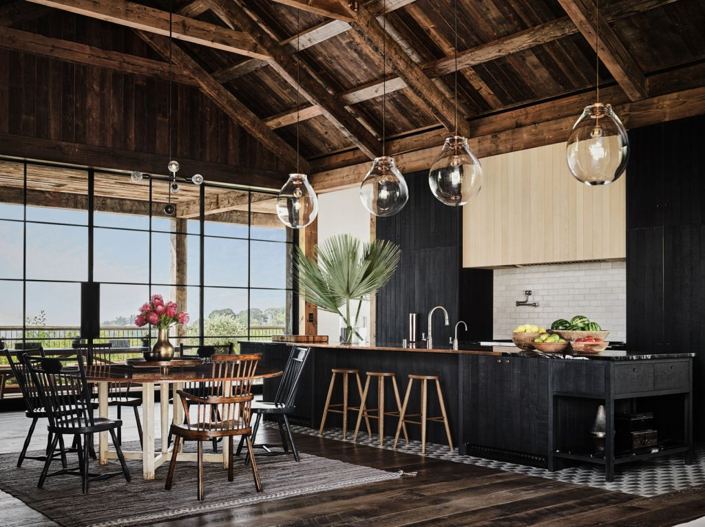 Large kitchen with unfinished black cabinetry, stylish pendant lights, and wood floors.
