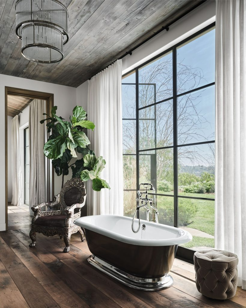 Elegant bathroom with freestanding tub, custom silver throne chair, and tufted ottoman.