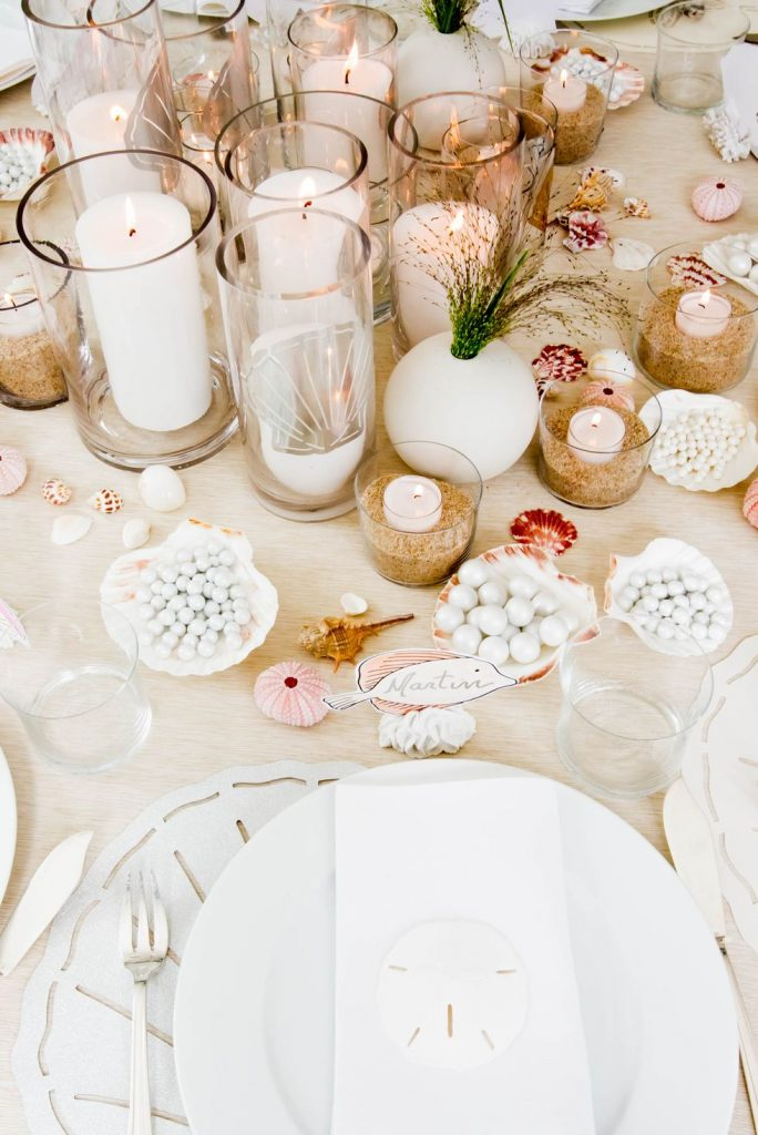 An ocean themed tablescape with white candles and seashells.