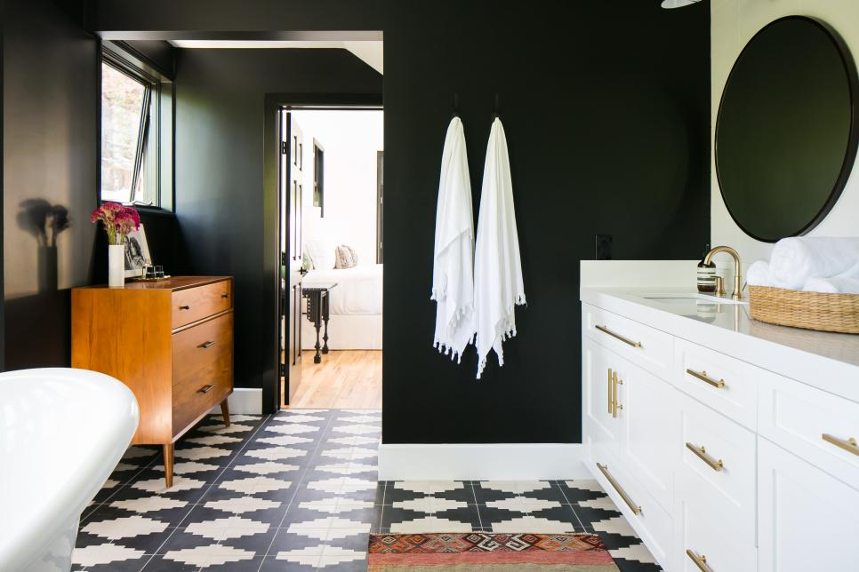 A bathroom with black walls, white cabinetry and Aztec patterned tile flooring.