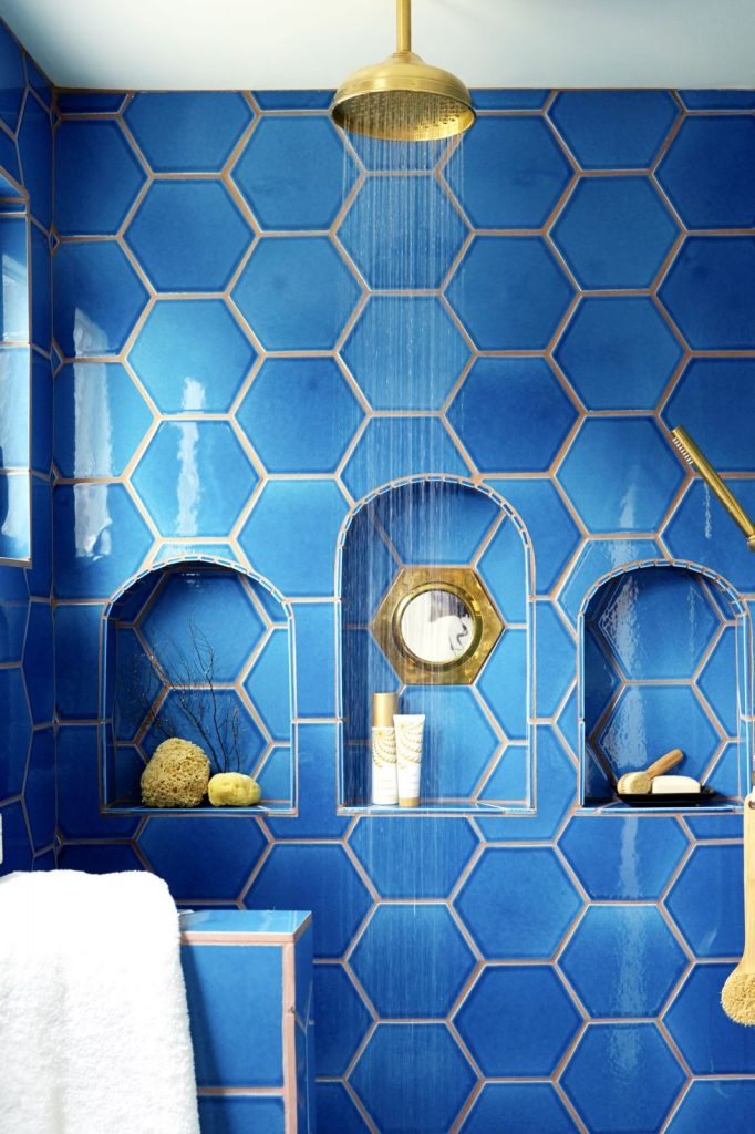 A shower with built-in shelves and bright blue hexagon tiles.