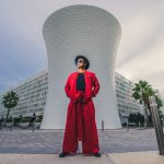 """Orlando artist JEFRË in front of """"The Beacon"""" structure and code wall parking garage in Lake Nona."""