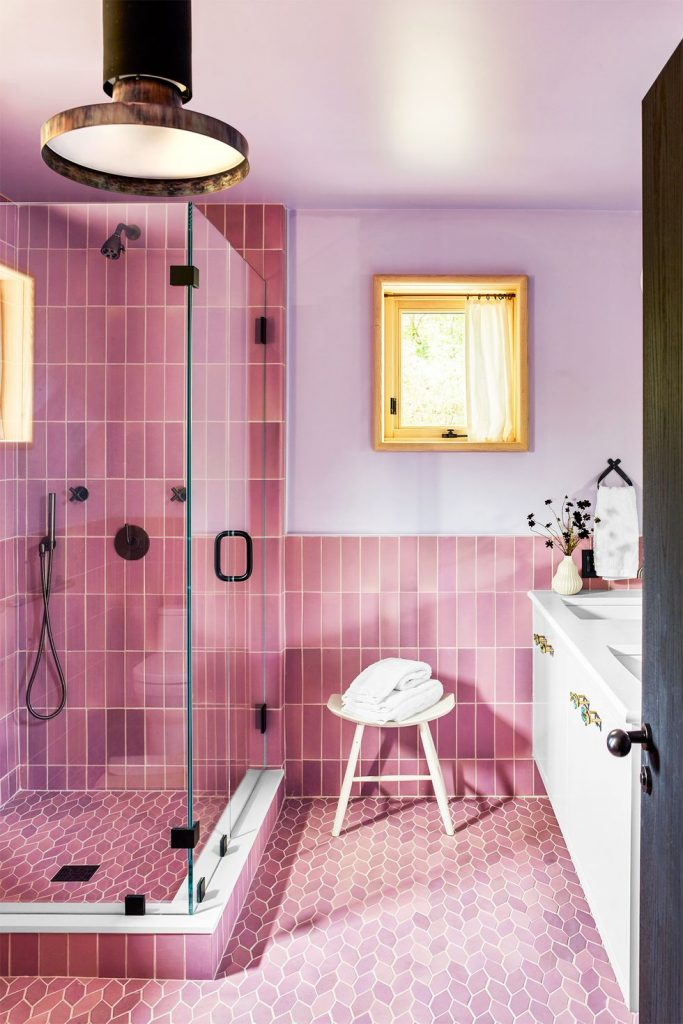A bathroom with bubblegum pink subway tiles and leaf shaped floor tiles in the same color.