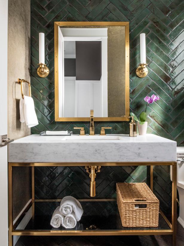 A bathroom vanity with a emerald green herringbone tile backdrop.