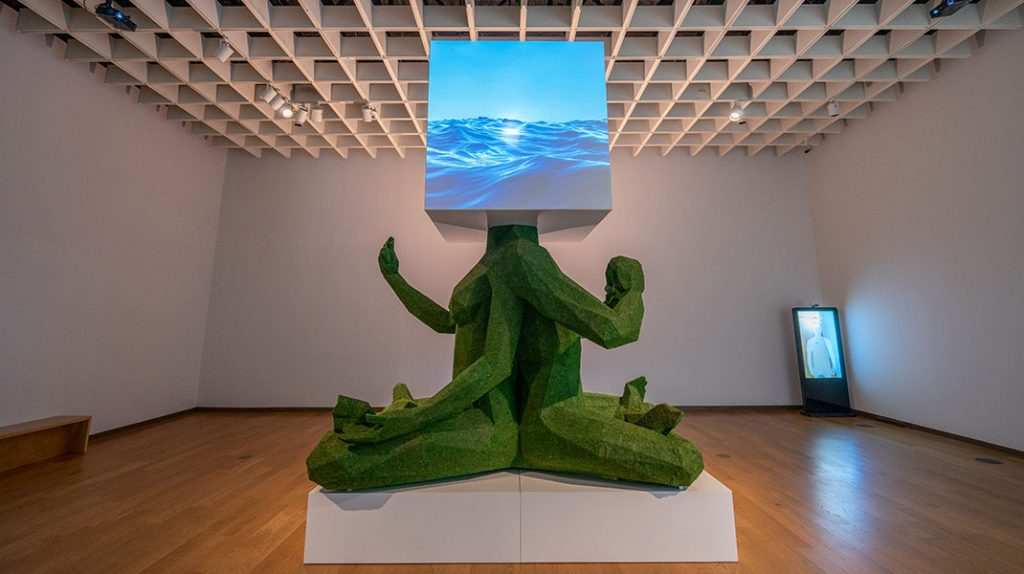 """JEFRË's piece entitled """"One Peace, One Love"""" which is two human figures sitting cross-legged back to back with a digital cube as their head."""