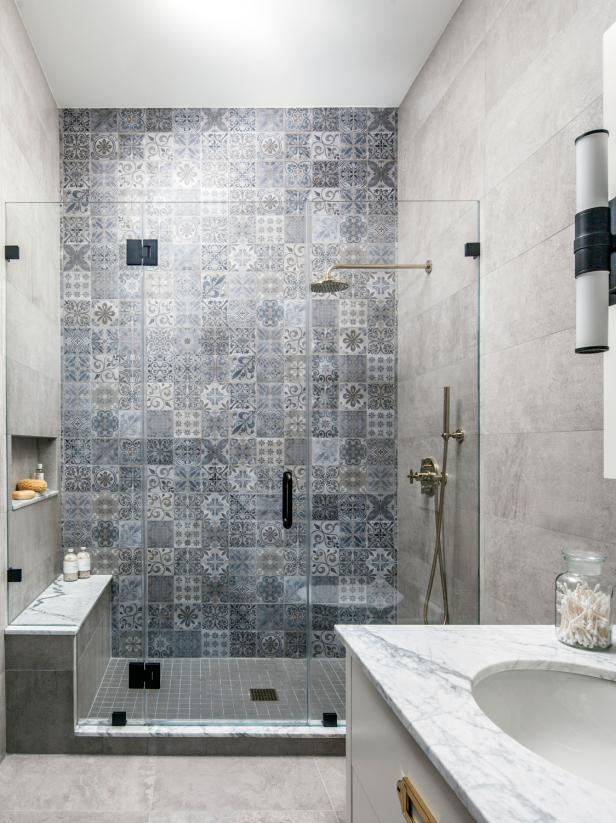 A shower with intricate tile design on one wall.