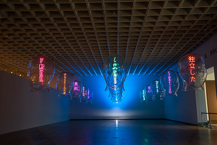 """JEFRË's installation called """"Talking Heads""""; clear human shaped heads hang from the ceiling with neon words inside."""