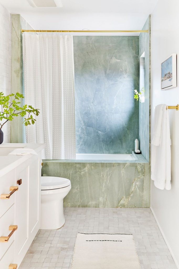 A bathroom with a shower and tub in light green marble and zellige floor tiles.